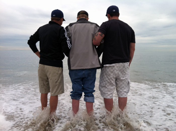 Dean Goetz, Lren Bill Kranksy and John Gomez stepping into the Pacific Ocean in California